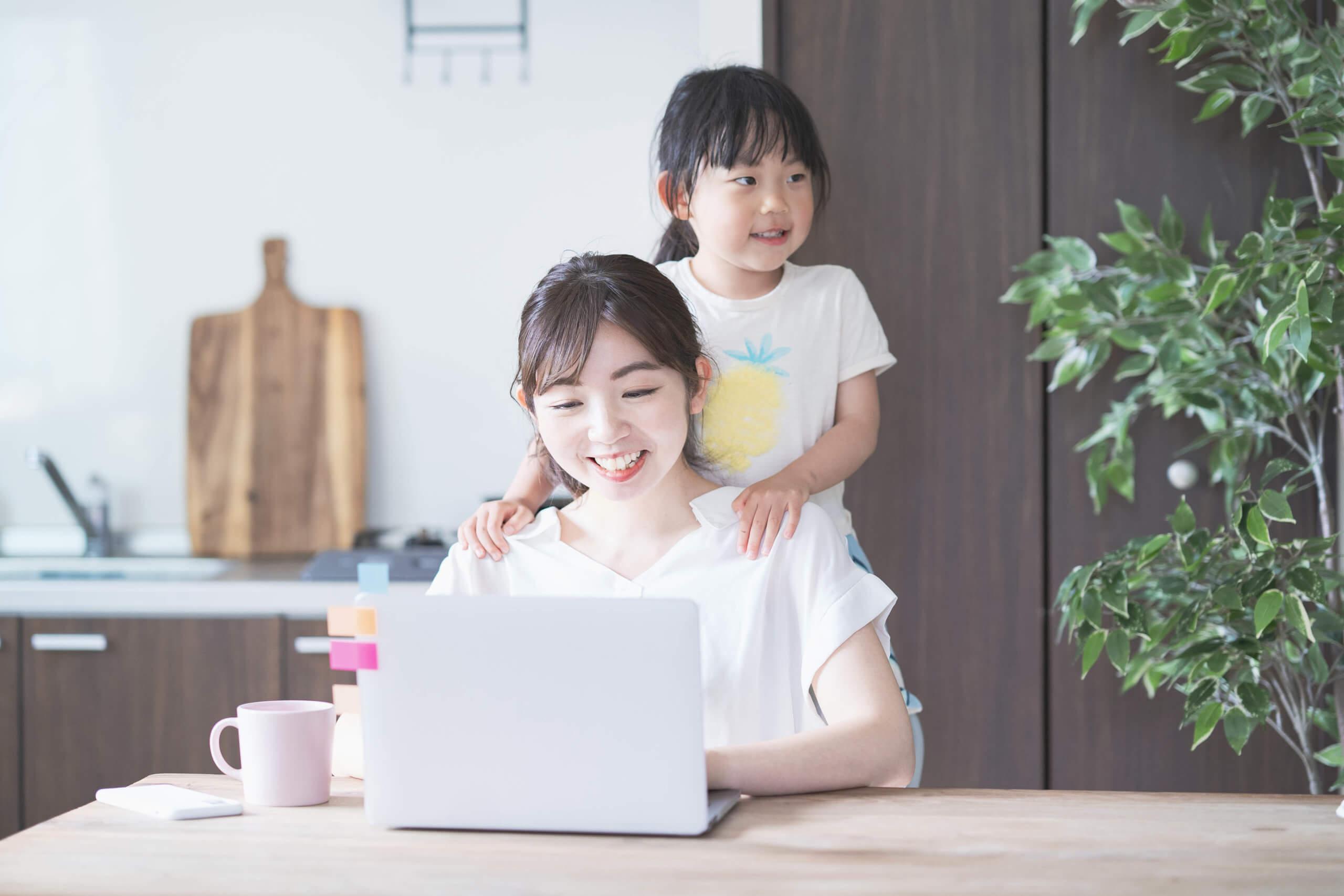 子供と遊びながらテレワークをする女性