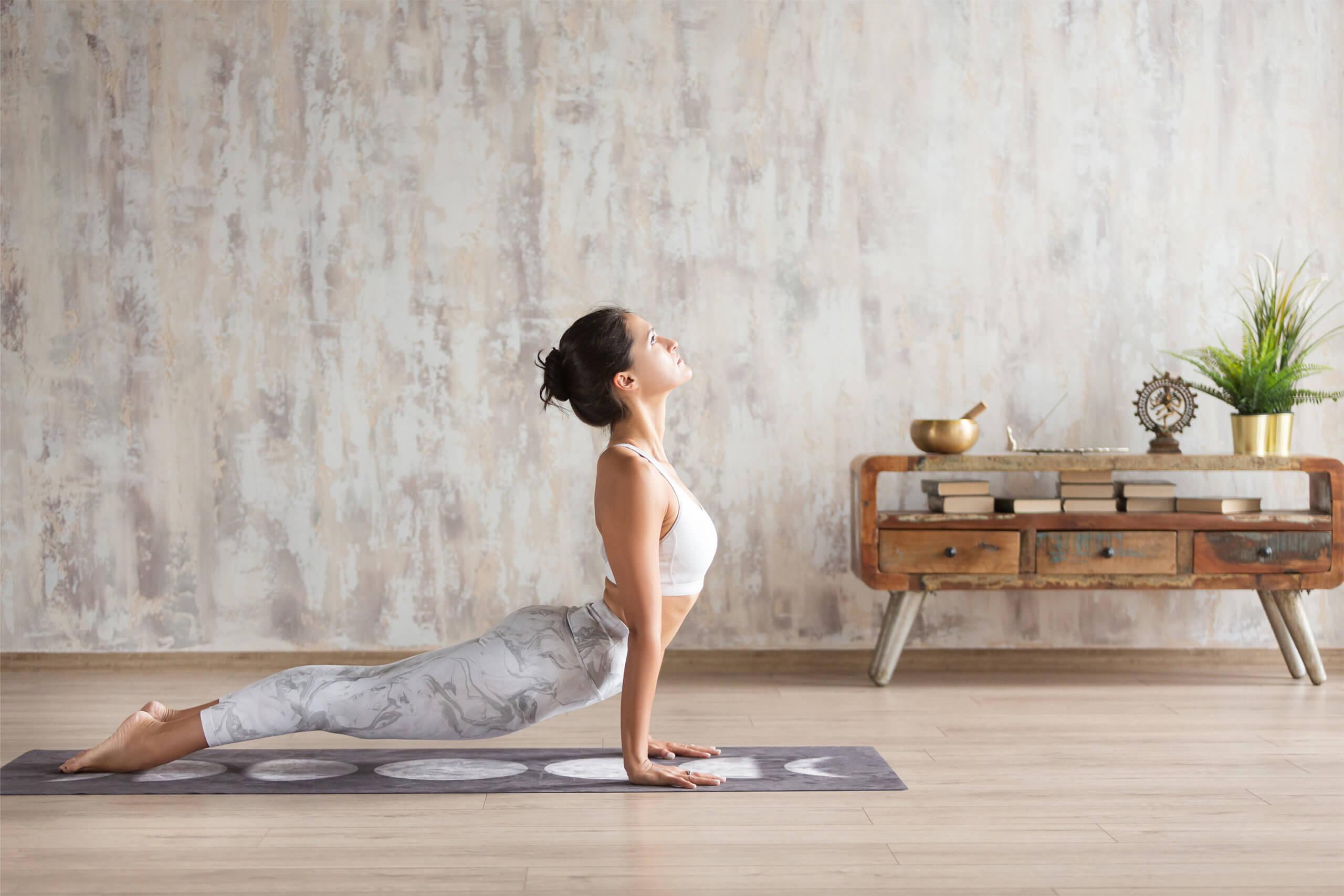 Young indian girl doing yoga fitness exercise indoor. Wellness c