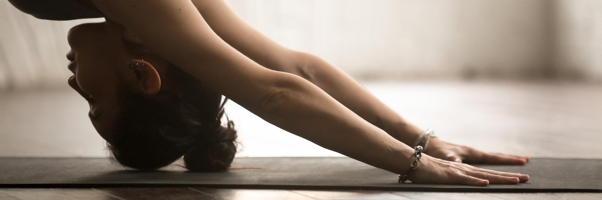Horizontal photo sportive woman practice yoga doing downward facing dog